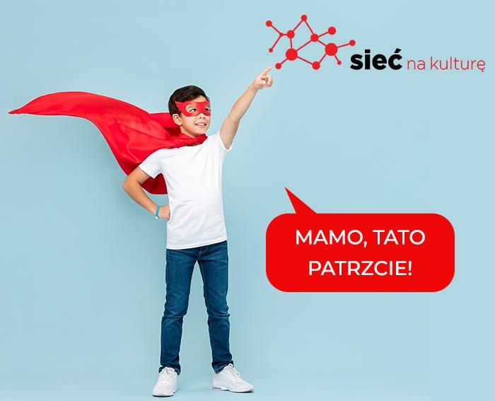 Chłopiec w pelerynie Superman wskazuje na logo Sieć na kulturę i mówi Mamo, Tato Patrzcie